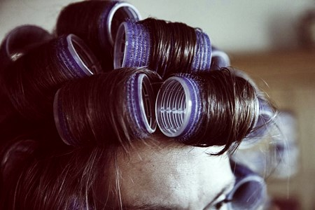 Woman drying and styling her hair in curlers